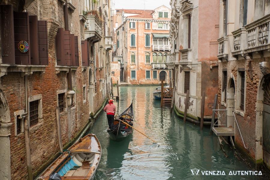 Gondolier rowing a gondola in Venice, Italy